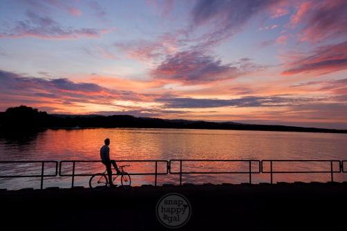 A lone cyclist watches a warm summer sunset over West Bay at the Open Space in Traverse City