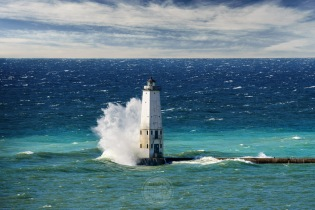 An autumn gale creates big waves with big swan-like splashes at the Frankfort Lighthouse in Lake Michigan