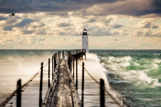 An autumn gale blows the spray from crashing waves over the pierhead at the Manistee Lighthouse