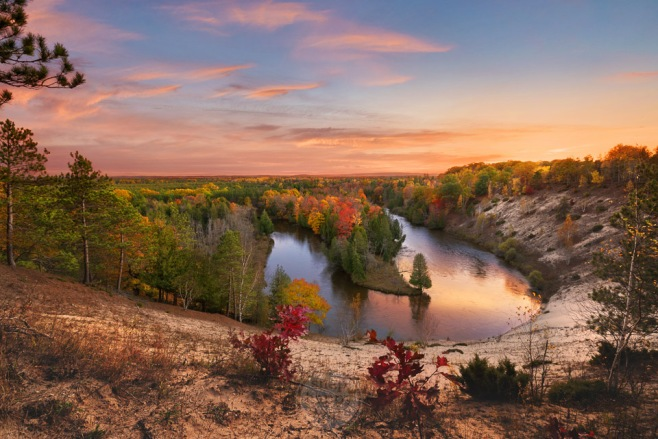Fall colors and a sunset highlight this hairpin turn in the Manistee River