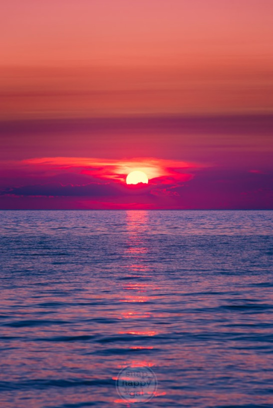 The sun sets in a fiery magenta glow into a shimmering Lake Michigan