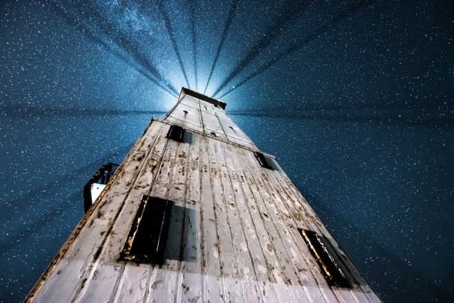 Light rays highlight the starry night sky under the Frankfort Lighthouse