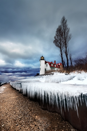 Pointy icicles hang below Point Betsie Lighthouse under moody skies