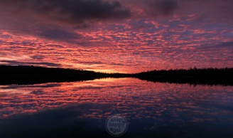 A dramatic red sunrise reflects in perfectly still waters