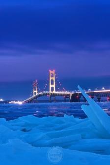 Shards of ice frame a golden Mackinac Bridge on a blue January night