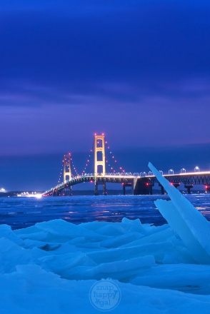 Shards of ice frame a golden Mackinac Bridge on a blue January night