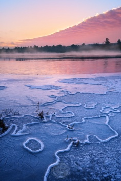 Mist rises off a freezing lake at sunrise