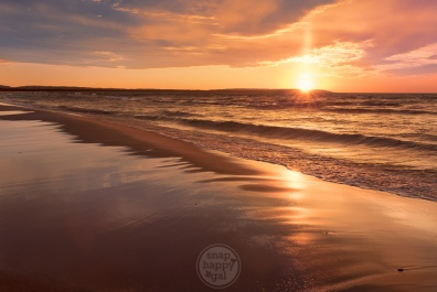 Peachy Pillar - A spire of light shines up from the sun along the Sleeping Bear Dunes National Lakeshore