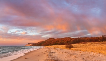 An expansive sunset featuring sunlit rain curtains over the Empire Bluffs