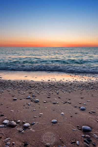 Beach pebbles and sand textures in the afterglow of a blue and gold sunset on Lake Michigan