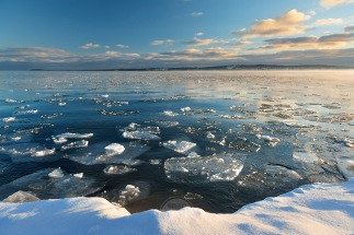 Chunks of ice bob in Lake Michigan in Traverse City on a golden winter morning
