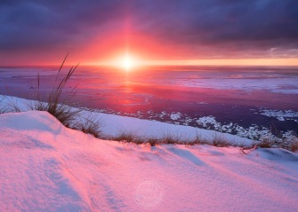 The sun bursts through a low cloud layer coloring the snow covered dunes above Lake Michigan a vibrant pink