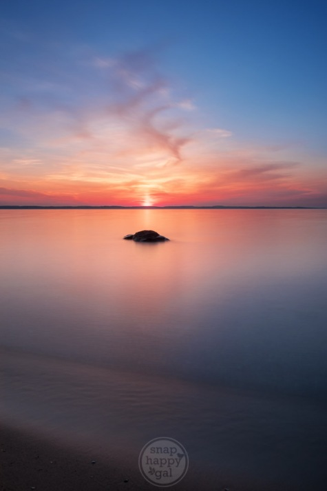 A single boulder sits in a still Lake Michigan at sunset