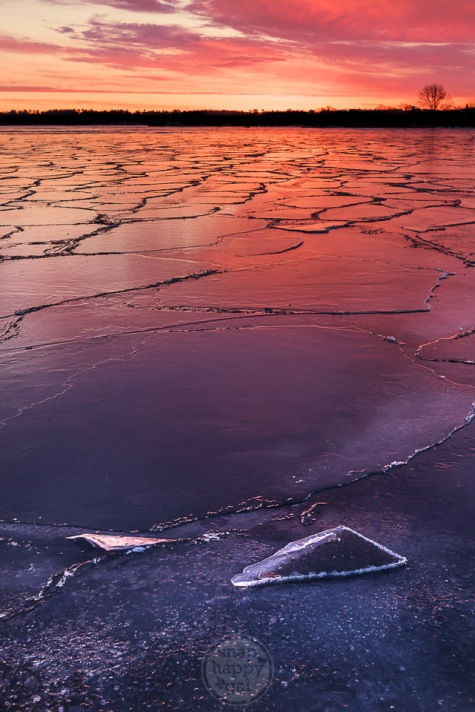 Shards of ice sit atop a cracked Lake Michigan during a red sunrise in Traverse City
