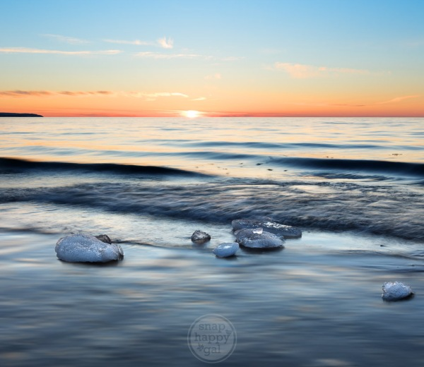 Chunks of crystalline ice sit in Lake Michigan's shallows during an orange and blue sunset