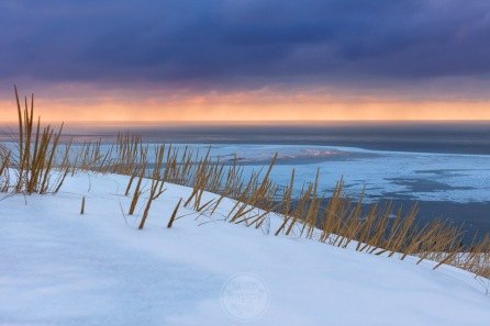 Dune grass peeks through snowpack perched above a partially frozen Lake Michigan in the Sleeping Bear Dunes