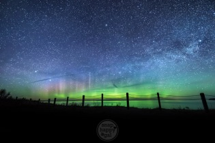 A beach fence silhouette stands against green northern lights and the Milky Way along the Lake Michigan shoreline in Glen Haven