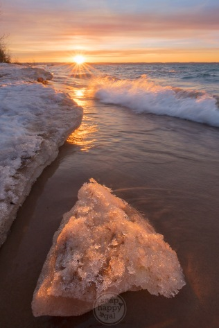 A chunk of fallen ice shelf catches the last rays of a warm winter sunset on Lake Michigan