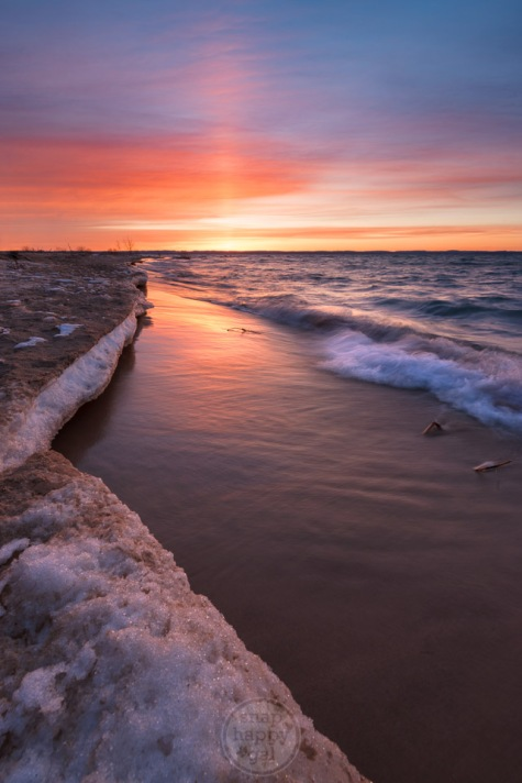 A pillar of last light during sunset illuminates an icy shore along Lake Michigan