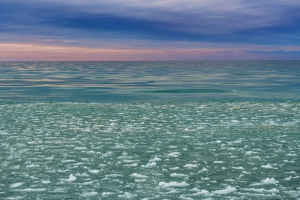Moody sky, mercurial water, and frozen ice pancakes on Lake Michigan in the winter