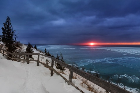 A red fireball sunset in a moody sky above a frozen Lake Michigan at Empire Bluffs
