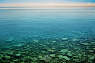 The rocky bottom stands out near a breakwall in Elberta, Michigan on a calm day