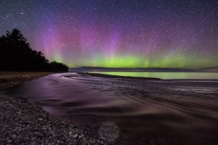 Shalda Creek flows gently into Lake Michigan under the light of the aurora and countless twinkling stars in the Sleeping Bear Dunes