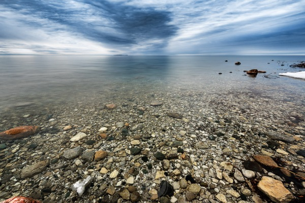 Rocky shallows in an eerily calm Lake Michigan on a moody day in Northport