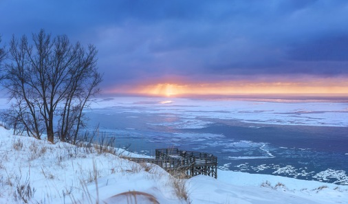 Golden sun rays highlight patches of ice on Lake Michigan from the Sleeping Bear Dunes main overlook in the winter