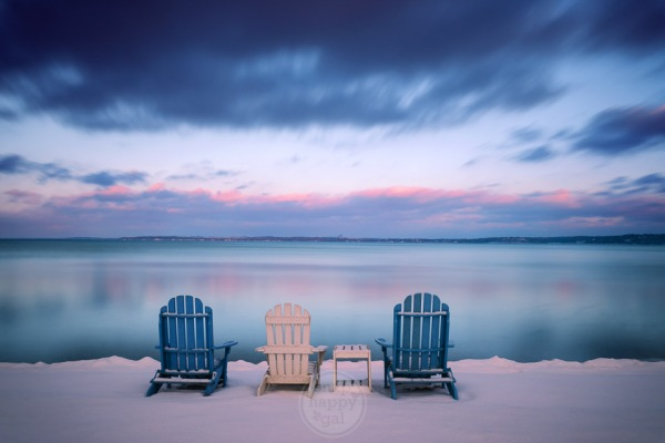 Three Adirondack chairs lined up on a snowy beach in Traverse City, Michigan