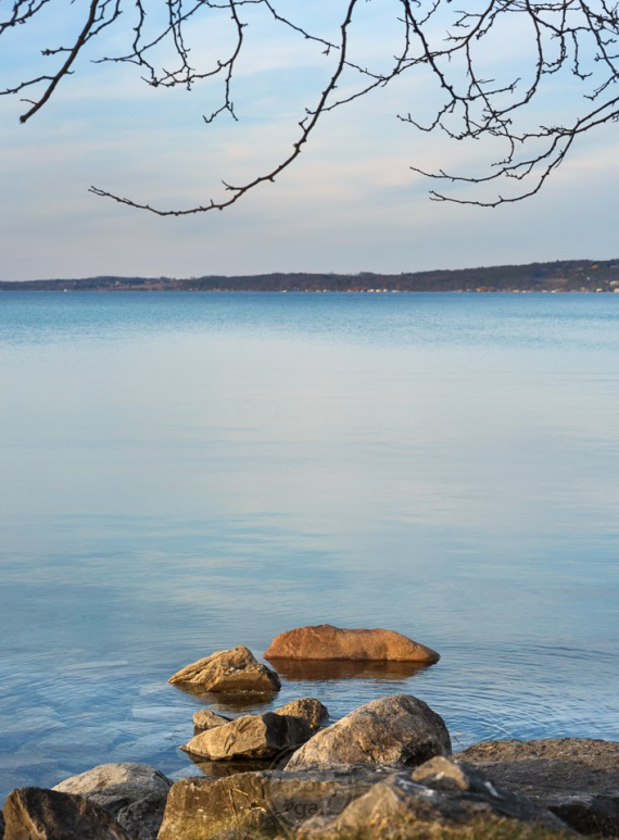 Smooth Lake Michigan waters dotted with stones and framed by branches