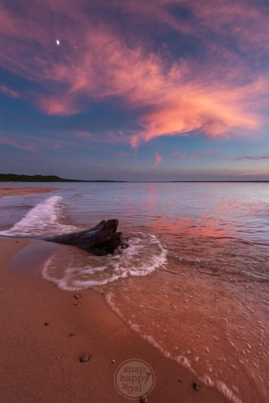 Lake Michigan's waters on East Grand Traverse Bay lap around driftwood under a crescent moon and swirling clouds