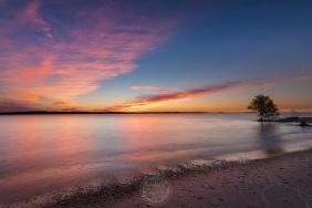 A vibrant summer sunset dances above a pebbly textured beach