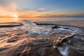 The Upper Peninsula's (Michigan) Hurricane River flows past some driftwood into Lake Superior at sunset