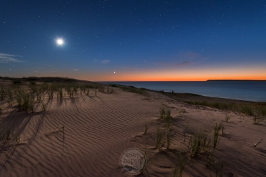 The moon and starry skies at twilight over Sleeping Bear Point, South Manitou Island, and Lake Michigan