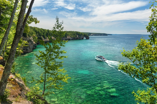 A cruise ship plies the waters of Lake Superior along the cliffs of the Pictured Rocks National Lakeshore