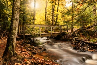 A footbridge crosses the creek above Chapel Falls in the Pictured Rocks National Lakeshore