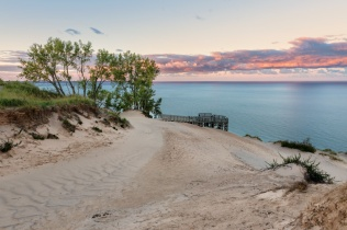 Post-storm clouds catch sunrise highlights over the main Lake Michigan overlook in the Sleeping Bear Dunes