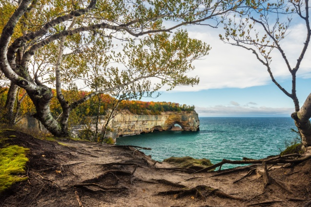 Perfectly curved trees frame a fall view of Lake Superior and Grand Portal Point in the Pictured Rocks National Lakeshore