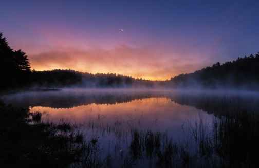 Morning fog lifts off a still lake under a sliver of crescent moon